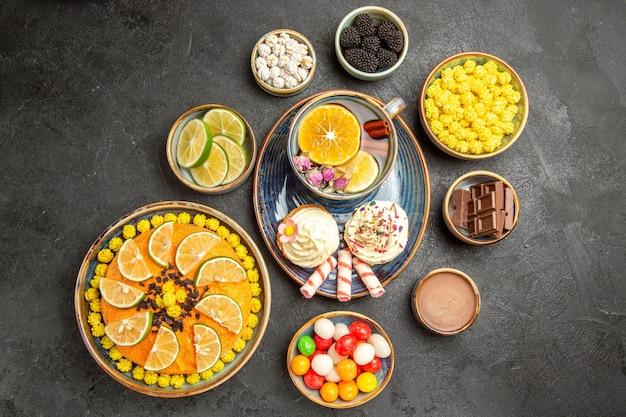 Draufsicht eine tasse kräutertee blauer teller mit cupcakes mit sahne eine tasse kräutertee und süßigkeiten neben den schalen mit schokoladenbeeren zitrusfrüchten schokoladencreme und bonbons auf dem dunklen tisch