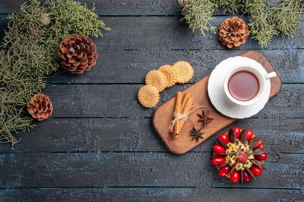 Draufsicht eine tasse tee anissamen und zimt auf hölzernem servierteller kekse tannenzapfen beerenkuchen auf dunklem holzboden