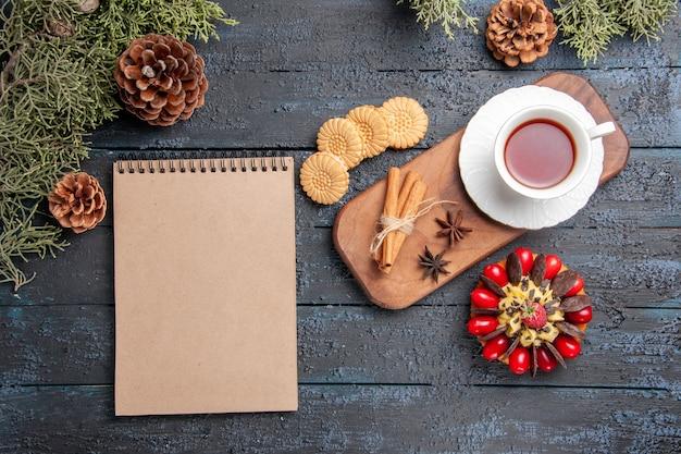 Draufsicht eine tasse tee anissamen und zimt auf hölzernem servierteller kekse tannenzapfen beerenkuchen und ein notizbuch auf dunklem holztisch