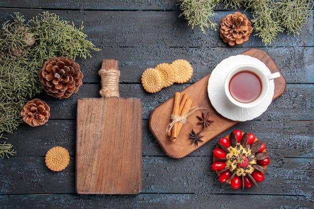 Draufsicht eine tasse tee anissamen und zimt auf hölzernem servierteller kekse tannenzapfen beerenkuchen und schneidebrett auf dunklem holztisch