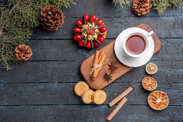 Draufsicht eine tasse tee anissamen und zimt auf hölzernem servierteller tannenzapfen beerenkuchen getrocknete orangen und verschiedene kekse auf dunklem hölzernem hintergrund
