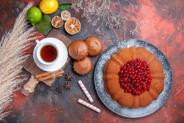 Draufsicht eine tasse tee ein kuchen mit roten johannisbeeren eine tasse schwarzer tee zimt auf dem schneidebrett