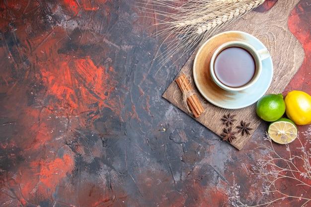 Draufsicht eine tasse tee eine tasse tee sternanis zitrone limette zimt auf dem brett