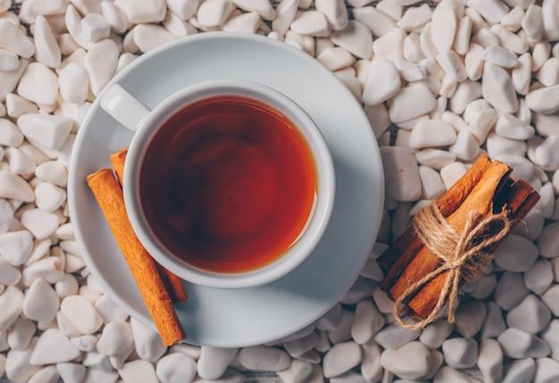 Draufsicht eine tasse tee mit trockenem zimt auf weißem flussfelsenhintergrund. horizontal