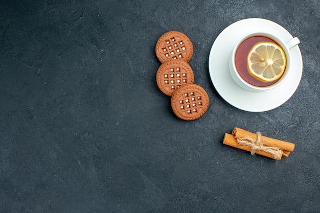 Draufsicht eine tasse tee mit zitronen-zimtstangen-keksen auf freiem raum der dunklen oberfläche