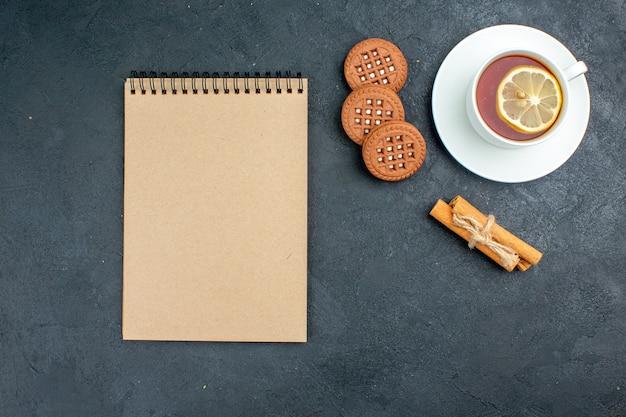 Draufsicht eine tasse tee mit zitronen-zimtstangen-keksen notizblock auf dunkler oberfläche
