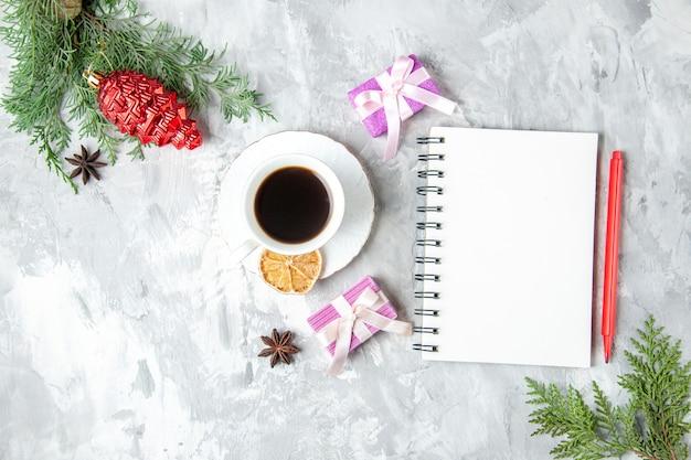 Draufsicht eine tasse tee notizbuch bleistift kleines geschenk weihnachtsbaum spielzeug auf grauem hintergrund