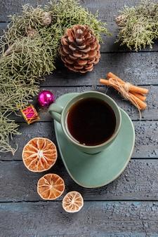 Draufsicht eine tasse tee tannenbaumzweige weihnachtsspielzeug getrockneten orangenzimt auf dunklem holztisch