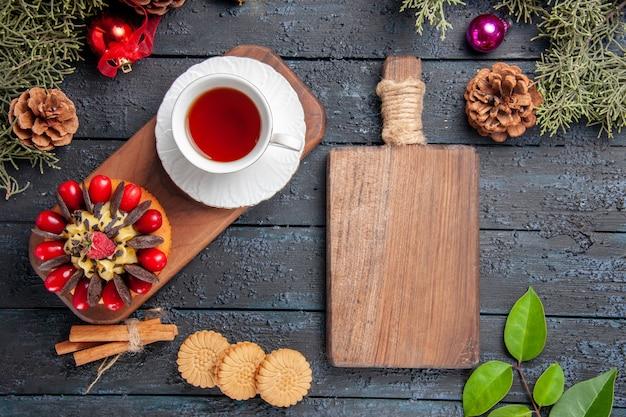 Draufsicht eine tasse tee und beerenkuchen auf hölzernem servierteller tannenzapfen-weihnachtsspielzeugblätter und ein schneidebrett auf dunklem holztisch