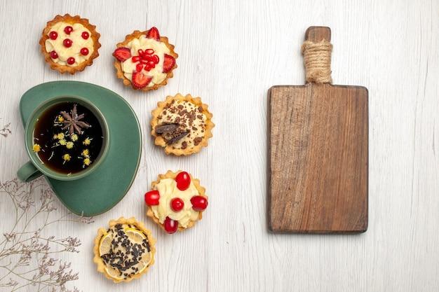 Draufsicht eine tasse tee und verschiedene kekse links und ein schneidebrett rechts vom weißen holztisch