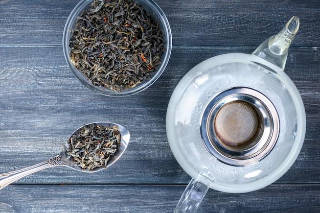 Draufsicht eine teekanne des heißwassers und der schüssel mit teeblatt auf dem grauen hölzernen schreibtisch. trinken sie zum entspannen.