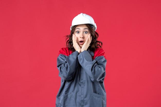 Draufsicht einer ängstlichen baumeisterin in uniform mit schutzhelm auf isoliertem rotem hintergrund