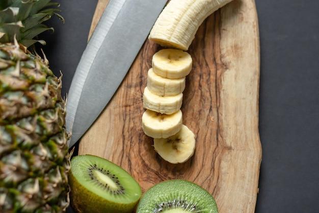 Draufsicht einer ananas auf dem tisch mit gehackten bananen und kiwis auf einem hölzernen schneidebrett