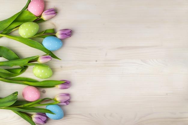 Draufsicht einer bunten ostereier im korb und in den lila tulpen auf einem hellen holzhintergrund mit nachrichtenraum.