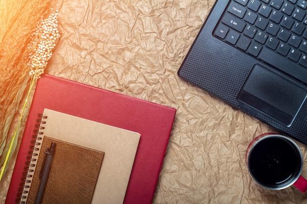 Draufsicht einer computer-, laptop-, notizbuch-, stift-, schalenkaffee- und büroarbeitsplatzweinleseart