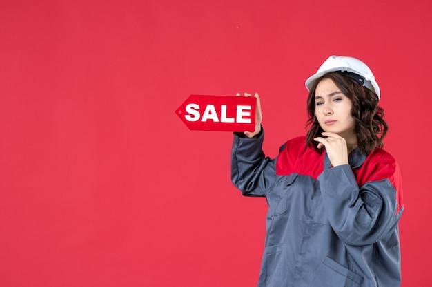 Draufsicht einer denkenden arbeiterin in uniform, die einen schutzhelm trägt und das verkaufssymbol auf isoliertem rotem hintergrund zeigt