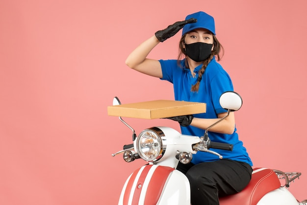 Draufsicht einer ehrgeizigen kurierin mit medizinischer maske und handschuhen, die auf einem roller sitzt und bestellungen auf pastellfarbenem pfirsichhintergrund liefert