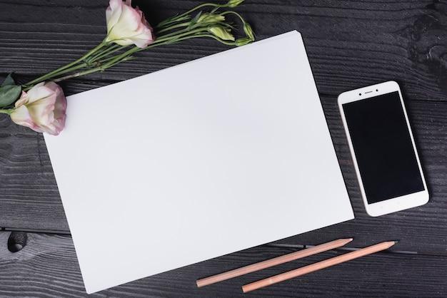 Draufsicht einer eustoma-blume; leeres weißes papier; buntstifte und handy auf schreibtisch aus holz
