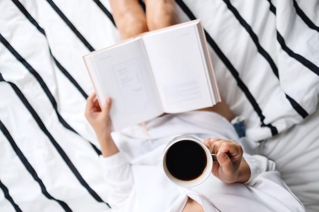 Draufsicht einer frau, die buch liest und heißen kaffee in einem weißen gemütlichen bett zu hause am morgen trinkt