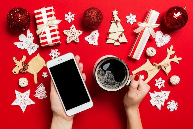 Draufsicht einer frau, die ein telefon in einer hand und einen tasse kaffee in einer anderen hand auf rot hält