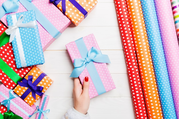 Draufsicht einer frau, die eine geschenkbox in ihren händen auf festlichem hölzernem hintergrund hält