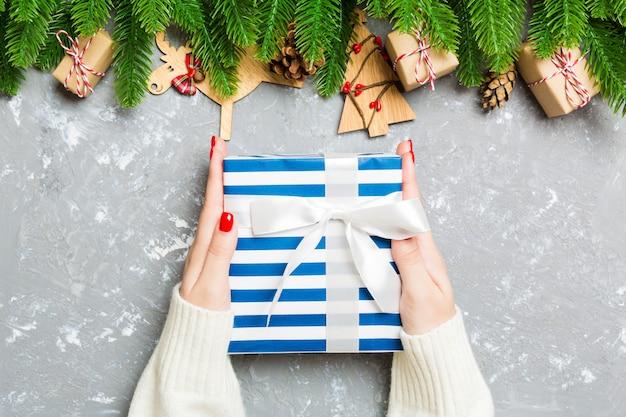 Draufsicht einer frau, die eine geschenkbox in ihren händen auf festlichem zement hält