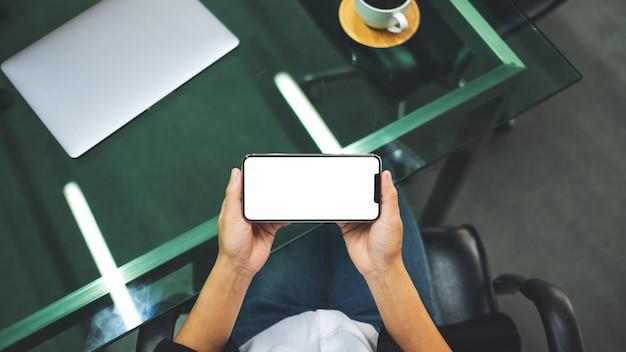 Draufsicht einer frau, die handy mit leerem weißen desktop-bildschirm mit laptop und kaffeetasse auf dem tisch hält