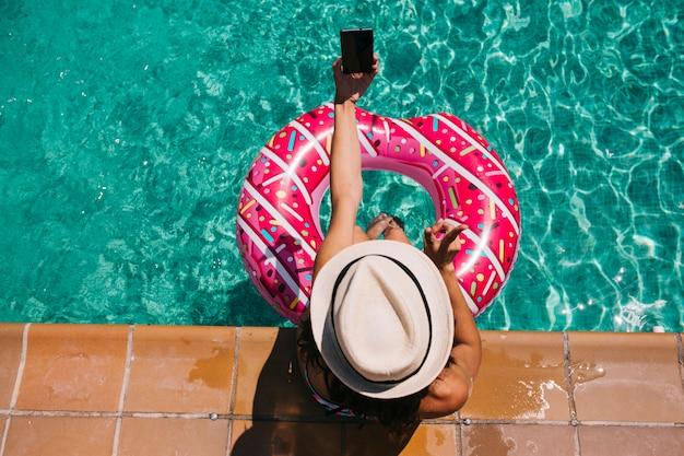 Draufsicht einer frau, die im pool mit rosa schaumgummiringen am heißen sonnigen tag sich entspannt sommerferien idyllisch, sonnenbräune genießend frau im bikini und in einem hut feiertage und sommerlebensstil sie benutzt handy