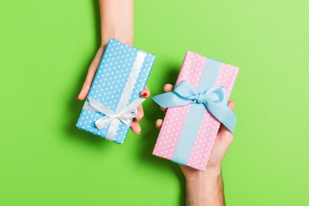 Draufsicht einer frau und des mannes, die geschenke auf colful hintergrund austauschen. paar geben einander geschenke. schließen sie oben von der herstellung des überraschungsfeiertagskonzeptes