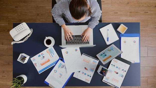 Draufsicht einer geschäftsfrau, die am schreibtisch sitzt und das fachwissen der finanzbuchhaltung eingibt