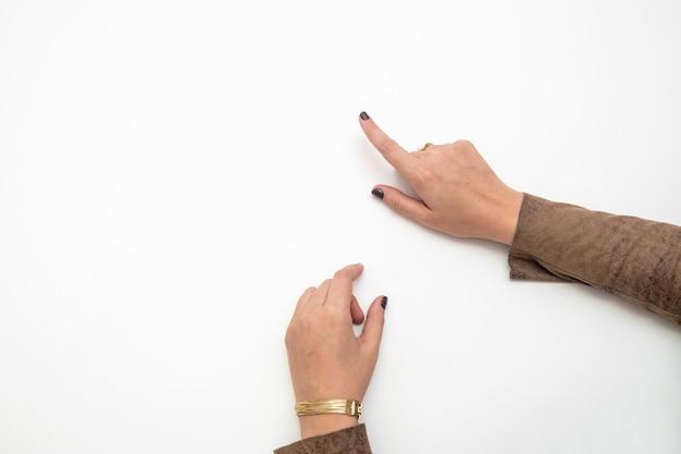 Draufsicht einer geschäftsfrau, die mit ihren händen mit kopienraum auf etwas zeigt.