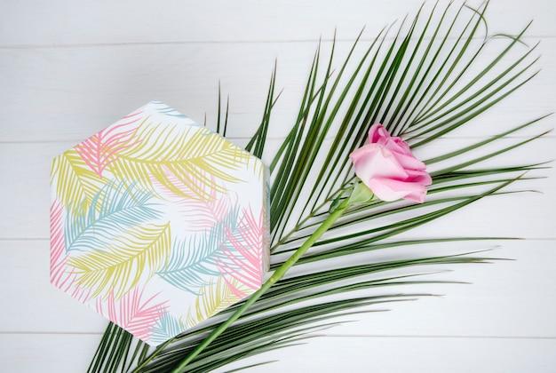 Draufsicht einer geschenkbox mit rosa farbe rose und palmblatt auf weißem hintergrund