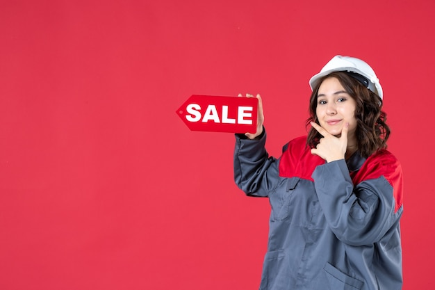 Draufsicht einer glücklichen arbeiterin in uniform, die einen schutzhelm trägt und das verkaufssymbol auf isoliertem rotem hintergrund zeigt