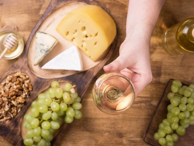 Draufsicht einer hand, die ein glas weißwein neben frischen trauben auf einem holztisch hält. leckere käse. leckere walnüsse. frühstück