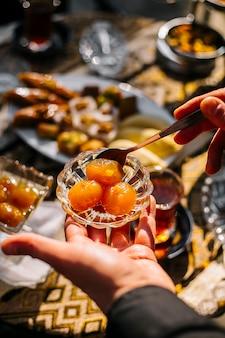 Draufsicht einer hand, die eine kleine glasuntertasse mit aprikosenmarmelade hält