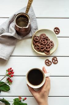 Draufsicht einer hand, die eine tasse kaffee, kaffeekanne und mit schokolade bedeckte brezeln auf einer weißen holzoberfläche hält. zusammensetzung des frühstücks oder der kaffeepause.
