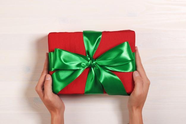 Draufsicht einer hand, die einen roten kasten mit einem geschenk mit einem grünen band hält.