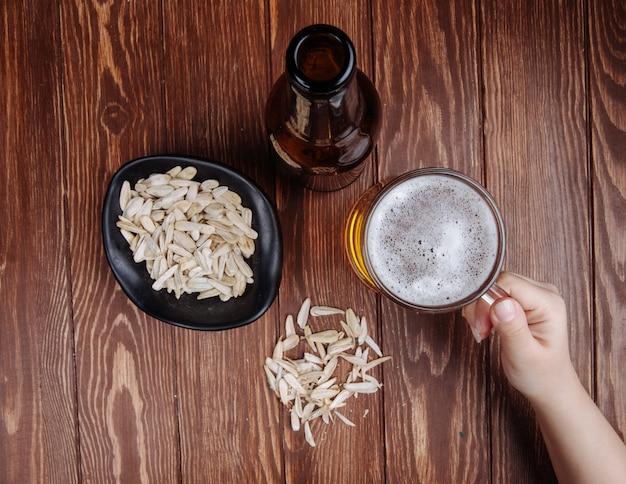 Draufsicht einer hand mit einem becher bier und einer flasche bier mit salzigem snack sonnenblumenkerne in einer schüssel auf rustikalem holz