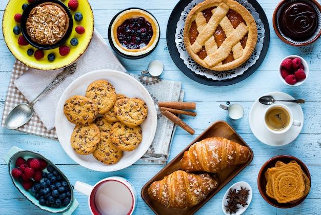 Draufsicht einer hölzernen tabelle voll der kuchen, der früchte, des kaffees, der kekse, der gewürze und mehr