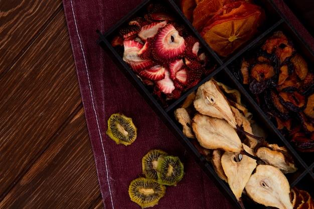 Draufsicht einer holzkiste mit verschiedenen getrockneten früchten birnen-erdbeer-kiwi und pflaumenscheiben auf hölzernem hintergrund mit kopienraum