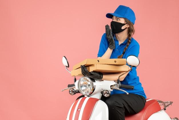 Draufsicht einer jungen besorgten emotionalen kurierin mit medizinischer maske und handschuhen, die auf einem roller sitzt und bestellungen auf pastellpfirsich liefert