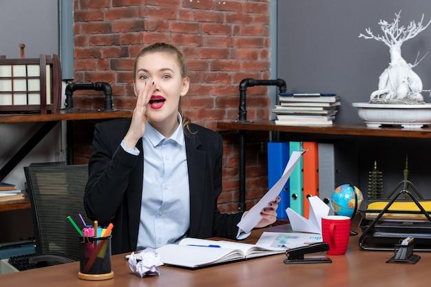 Draufsicht einer jungen dame, die an einem tisch sitzt und das dokument hält, das jemanden im büro anruft