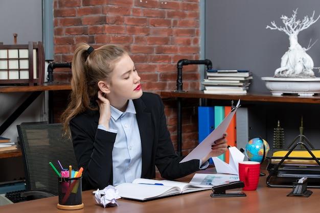 Draufsicht einer jungen frau, die an einem tisch sitzt und das dokument mit kopfschmerzen im büro hält