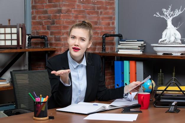 Draufsicht einer jungen frau, die an einem tisch sitzt und ein dokument hält, das neugierig auf etwas im büro ist