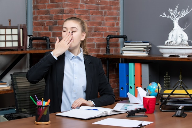 Draufsicht einer jungen frau, die an einem tisch sitzt und im büro gähnt