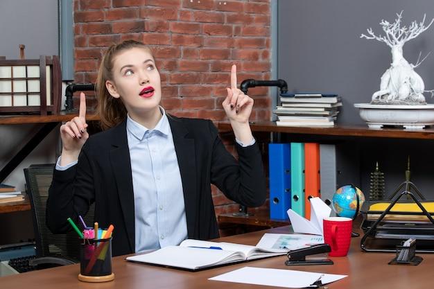 Draufsicht einer jungen frau, die an einem tisch sitzt und im büro nach oben zeigt