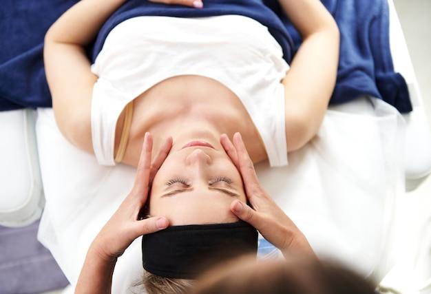 Draufsicht einer jungen frau, die auf einem massagetisch liegt und eine professionelle glättende und verjüngende gesichtsmassage genießt, die von einer kosmetikerin im spa-salon durchgeführt wird