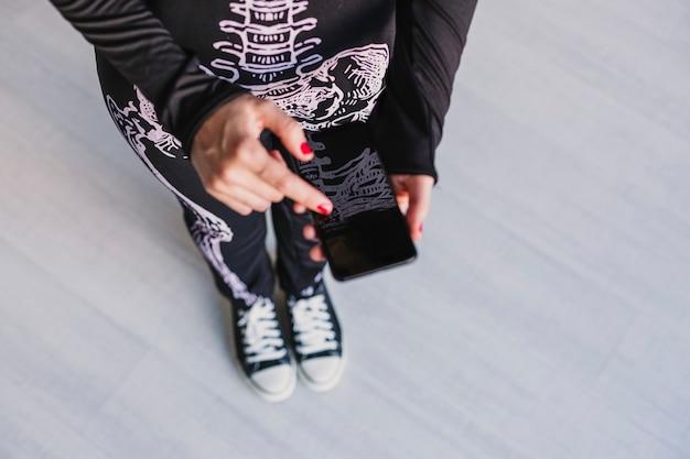 Draufsicht einer jungen frau, die handy verwendet. tragen eines schwarz-weißen skelettkostüms. halloween-konzept. drinnen. technologie
