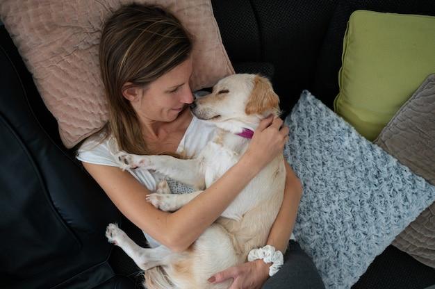 Draufsicht einer jungen frau, die mit ihrem süßen weißen hund kuschelt, der in ihrem schoß schläft.