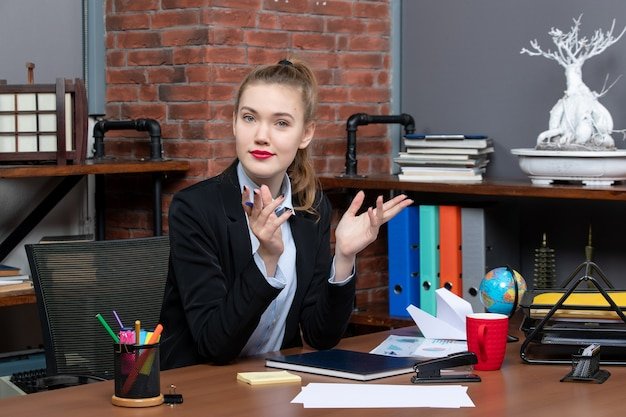 Draufsicht einer jungen neugierigen büroangestellten, die an ihrem schreibtisch sitzt und für die kamera posiert